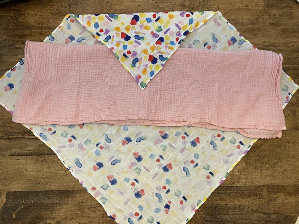 Use a rectangular muslin blanket under your main swaddle blanket to help hold down your little escape artist's arms.